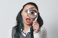 看照相机的一滑稽的年轻女人的画象通过在灰色背景的放大镜 免版税图库摄影
