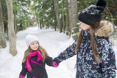 看照相机的两个女孩在冬天公园 库存图片