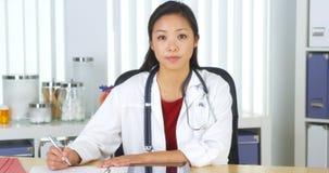 看照相机的亚裔医生书桌 免版税库存照片