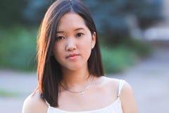 看照相机的亚洲美丽的女孩画象 免版税库存照片