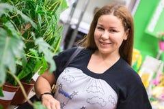 看照相机的俏丽的妇女,当站立与绿色植物时 免版税库存图片