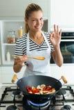 看照相机的健康年轻女人,当在家时烹调和混合在煎锅的食物在厨房里 免版税库存图片