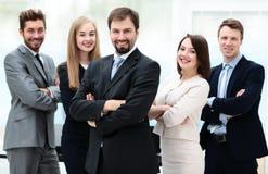 看照相机的典雅的工友在会议期间在办公室 免版税库存图片