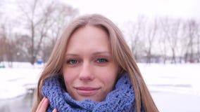 看照相机的冬天城市公园的美丽的蓝眼睛的妇女和改正她温暖的蓝色被编织的围巾  股票视频