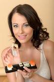 看照相机的可爱的少妇拿着寿司盘子  免版税图库摄影