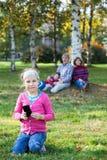 看照相机的女孩,当坐与手机,在背景时的家庭的草 免版税图库摄影