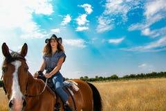 看照相机的女牛仔,当与西部马鞍和帽子时的骑乘马 库存照片
