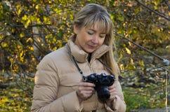 看照相机的妇女摄影师 免版税库存图片