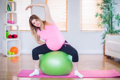 看照相机的孕妇坐锻炼球 库存图片