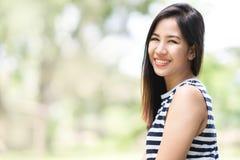 看照相机的年轻可爱的亚裔妇女画象微笑与确信和正面生活方式概念在室外公园 免版税库存图片