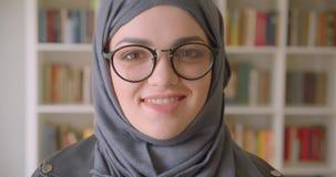 看照相机的年轻可爱的回教女生和玻璃特写镜头画象hijab的在大学图书馆里 股票录像