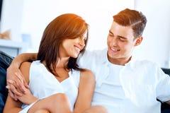 看照相机的年轻夫妇,当在家时坐 库存图片