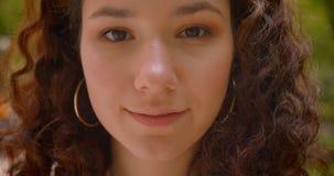 看照相机的年轻快乐的俏丽的长发卷曲白种人女性特写镜头画象户外在庭院 股票视频
