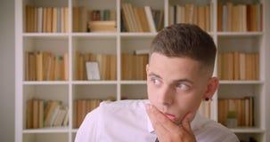 看照相机的年轻成功的可爱的商人特写镜头画象在图书馆里户内与书架  股票视频