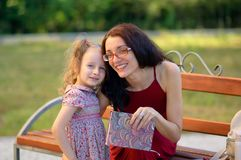 看照相机的年轻母亲和她逗人喜爱的矮小的女儿外部画象  妇女拿着一本书 孩子有 图库摄影