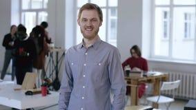 看照相机的年轻确信的成功的欧洲男性行政经理画象微笑在现代轻的办公室 股票视频