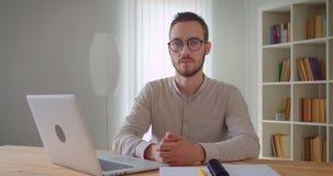 看照相机的年轻英俊的白种人商人特写镜头画象坐在膝上型计算机前面户内在 股票录像