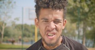 看照相机的年轻英俊的非裔美国人的男性篮球运动员特写镜头画象愤怒尖叫户外 股票录像