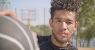 看照相机的年轻英俊的非裔美国人的男性篮球运动员特写镜头画象户外 股票视频
