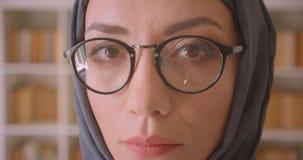 看照相机的年轻阿拉伯女性面孔和hijab特写镜头画象在玻璃的在图书馆里户内 股票视频
