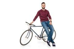 看照相机的微笑的人,当倾斜在自行车时 库存照片