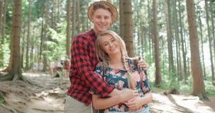 看照相机的微笑的夫妇,当放松在森林时 库存图片