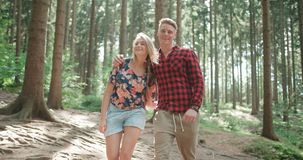 看照相机的微笑的夫妇,当放松在森林时 免版税库存图片