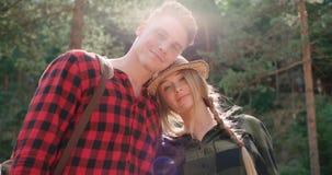 看照相机的微笑的夫妇,当放松在森林时 库存照片