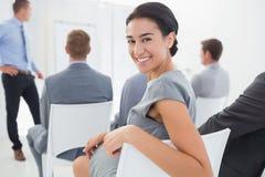 看照相机的微笑的女实业家在会议期间 免版税库存图片