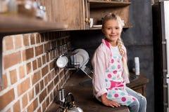 看照相机的微笑的小女孩画象,当坐柜台时 库存图片