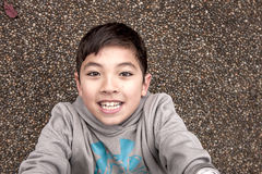 看照相机的微笑的男孩 免版税库存图片