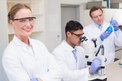 看照相机的微笑的科学家,当同事与显微镜一起使用时 免版税图库摄影