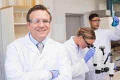 看照相机的微笑的科学家,当同事与显微镜一起使用时 图库摄影