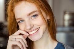 看照相机的微笑的红头发人妇女 库存图片