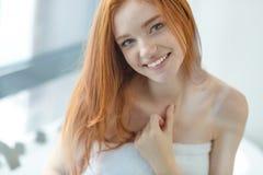 看照相机的微笑的红头发人妇女 免版税库存图片