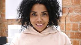 看照相机的微笑的美国黑人的妇女画象在办公室 股票录像