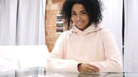 看照相机的微笑的美国黑人的妇女,坐在顶楼办公室 股票视频