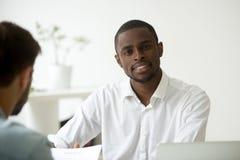 看照相机的微笑的非裔美国人的工作者在办公室 库存图片