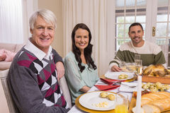 看照相机的快乐的家庭在圣诞晚餐期间 库存照片