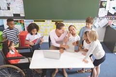 看照相机的愉快的女小学生,当他的同学和她的老师是arround每桌时 库存照片