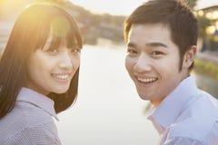 看照相机的愉快的年轻夫妇由河 免版税库存图片