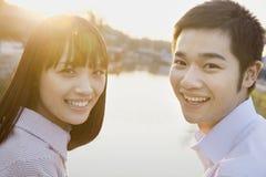 看照相机的愉快的年轻夫妇由河 免版税图库摄影
