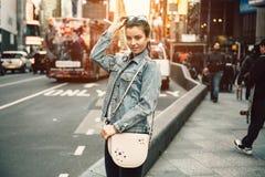 看照相机的愉快的年轻旅游妇女生活方式照片拿着袋子钱包和太阳镜在晴朗的繁忙的城市街道上 免版税库存照片