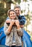 看照相机的愉快的年轻露营车夫妇 免版税库存图片