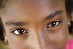 看照相机的愉快的年轻非洲女孩画象,微笑 免版税库存照片