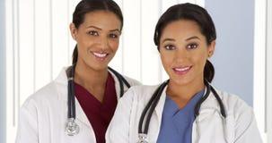 看照相机的拉美裔和非裔美国人的医生 免版税库存照片
