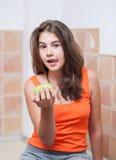 看照相机的橙色T恤杉的十几岁的女孩饮用一个绿色苹果在她的手 库存图片