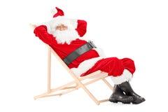看照相机的海滩睡椅的微笑的圣诞老人 图库摄影