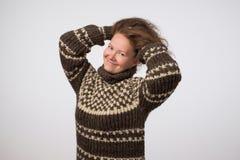 看照相机的温暖的毛线衣的微笑的欧洲夫人 查出在灰色背景 免版税库存图片