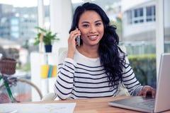看照相机的电话的微笑的亚裔妇女 免版税库存照片